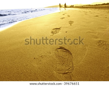 Low angle view of footprints receding on beach at sunset, children running in background. - stock photo