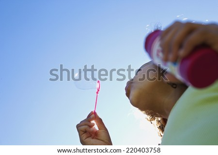Low angle view of girl blowing bubbles - stock photo