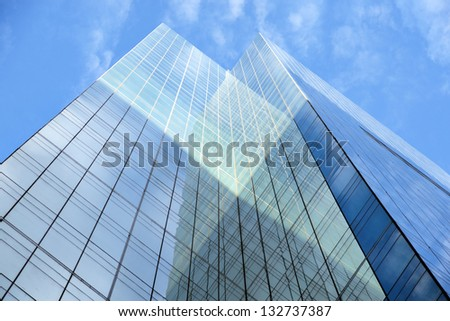 Low angle view of glass facade of tall office building on blue sky
