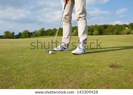 low angle view of golfer putting ball on green - stock photo