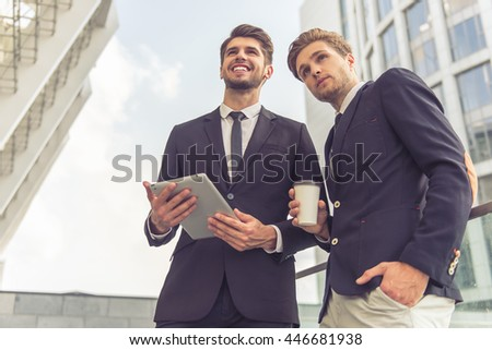 Low angle view of handsome young businessmen in classic suits with tablet and cup of coffee looking forward and smiling, standing outside the office building - stock photo