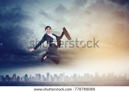 Low angle view of happy businesswoman holding a suitcase while jumping on the road with skyscraper background