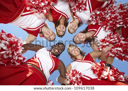 Low angle view of happy cheerleaders forming a huddle against clear sky - stock photo