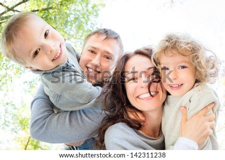 Low angle view of happy family in autumn park - stock photo