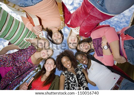 Low angle view of happy friends forming huddle against sky