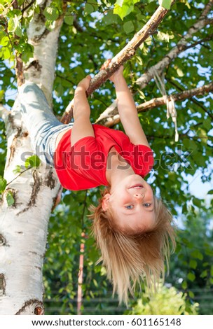 Low angle view of happy girl wearing red t-shirt hanging upside down from a birch tree looking at camera enjoying summertime