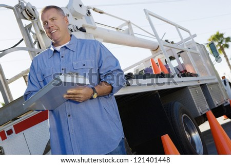 Low angle view of happy male mechanic holding clipboard with truck in background - stock photo