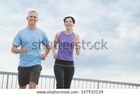 Low angle view of happy mature couple jogging against cloudy sky - stock photo