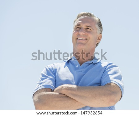 Low angle view of happy mature man looking away with arms crossed against clear sky