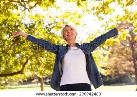 low angle view of happy mid age woman with arms outstretched outdoors - stock photo