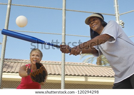 Low angle view of happy multi ethnic female friends playing baseball - stock photo