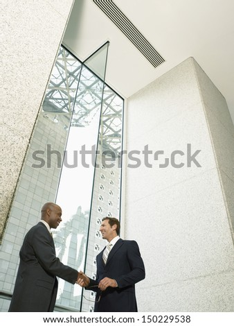 Low angle view of happy multiethnic businessmen shaking hands in office building - stock photo