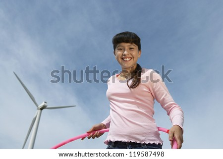 Low angle view of happy teenage girl with hula hoop against wind turbine and cloudy sky - stock photo
