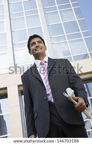 Low angle view of happy young businessman with newspaper standing in front of office building - stock photo