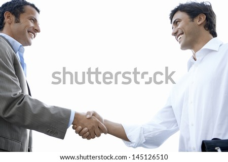 Low angle view of happy young businessmen shaking hands while standing against clear sky - stock photo
