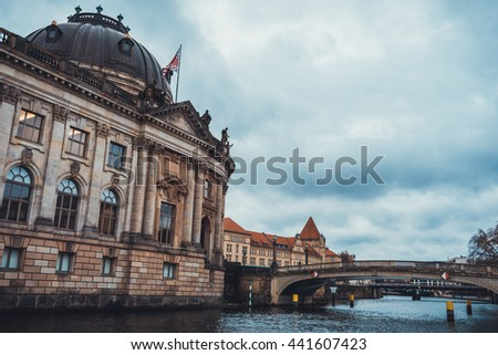 Low Angle View of Historical Bode Art Museum as seen from River with Small Bridges Crossing to Museum Island on Overcast Day with Storm Clouds, Berlin, Germany