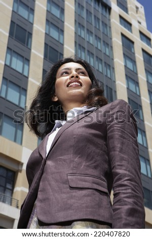 Low angle view of Indian businesswoman in urban scene - stock photo