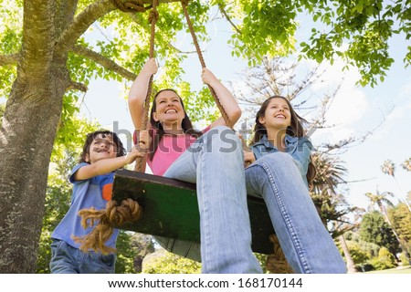 Low angle view of kids pushing mother on swing in playground - stock photo