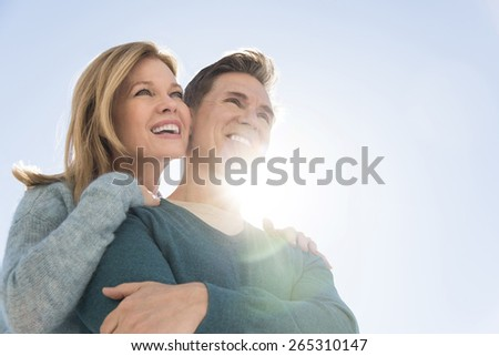 Low angle view of loving couple smiling together while looking away against clear sky