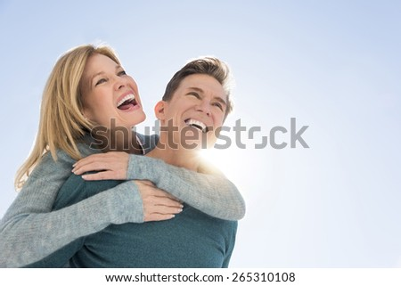 Low angle view of loving man giving piggyback ride to happy woman against clear sky - stock photo