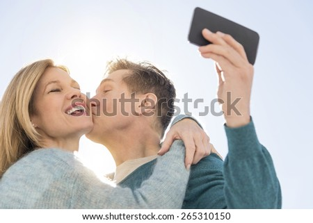 Low angle view of loving mature man kissing woman while taking self portrait on cell phone against sky