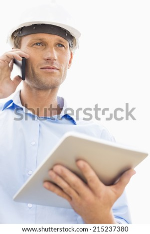 Low angle view of male architect with digital tablet using cell phone against sky - stock photo