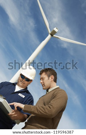 Low angle view of male engineers in discussion against wind turbine