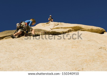 Low angle view of man assisting friend climbing rock against clear blue sky - stock photo