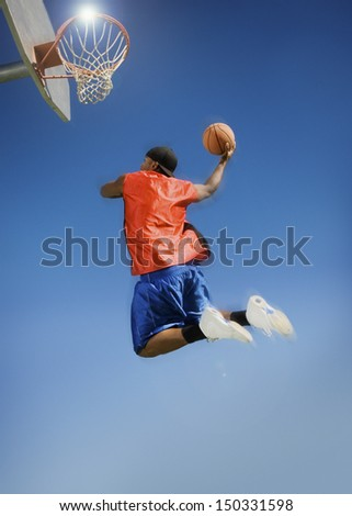 Low angle view of man dunking basketball into hoop against clear blue sky - stock photo