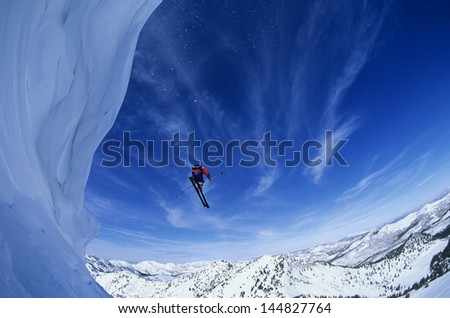 Low angle view of man jumping from mountain ledge against sky - stock photo