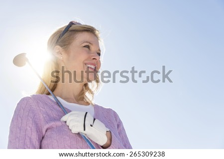 Low angle view of mature woman holding golf club against sky - stock photo