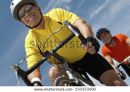 Low angle view of men riding bicycles against sky - stock photo