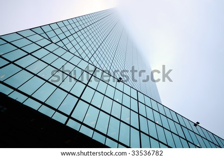 Low angle view of modern skyscraper disappearing in the fog. Abstract composition ideal for business concept or background.