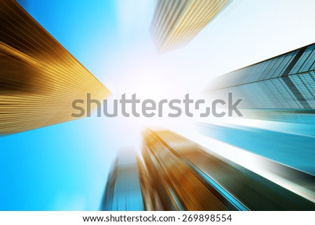 low angle view of modern skyscraper in blur motion - stock photo