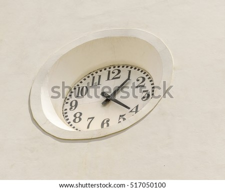 Low angle view of modern wall clock at white wall building facade in Recife, Brazil