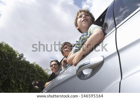 Low angle view of mother and two boys leaning through car window - stock photo