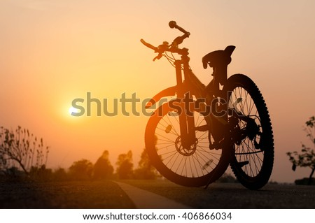 low angle view of mountain bike on trail at sunrise - stock photo