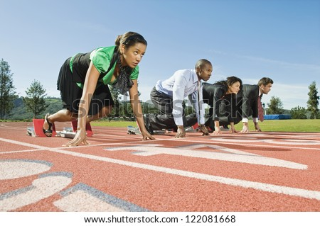 Low angle view of multi ethnic business people at starting position on race track - stock photo
