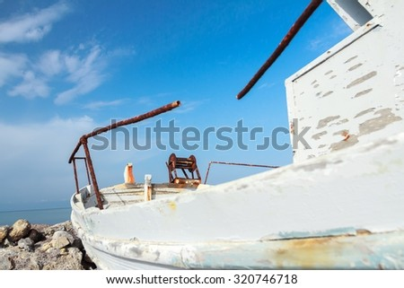 Low angle view of old wooden fishing boat with peeling white paint on Greek Kos island - stock photo