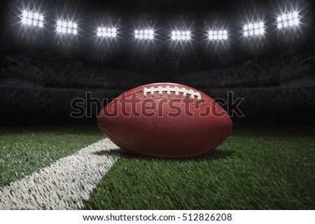 Low angle view of professional style football on yard line of field under stadium lights