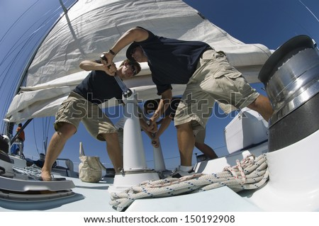 Low angle view of sailors operating windlass on yacht - stock photo