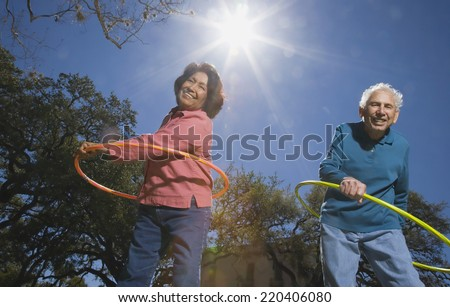 Low angle view of senior couple with plastic hoops - stock photo
