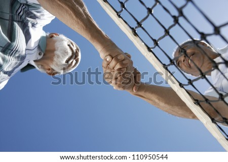 Low angle view of senior tennis players shaking hands against clear sky - stock photo