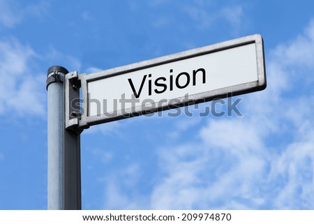Low angle view of signpost with Vision sign against sky - stock photo