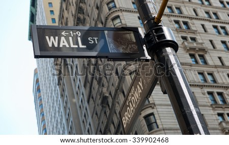 Low Angle View of Signs at Intersection of Wall Street and Broadway Street, Affixed to Post with View of Highrise Buildings in Background, New York City, New York, USA - stock photo