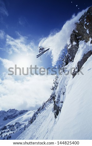 Low angle view of skier jumping from mountain against cloudy sky - stock photo