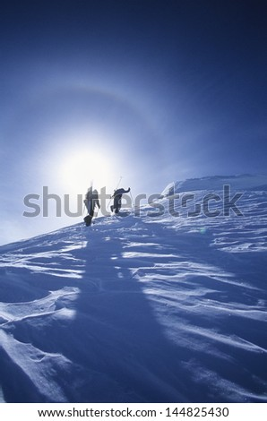Low angle view of skiers hiking to mountain summit - stock photo