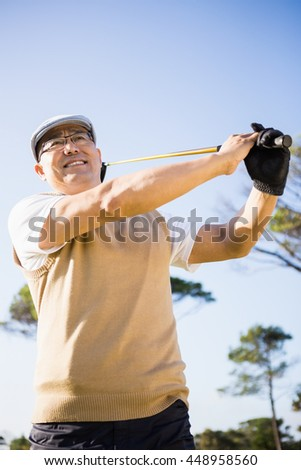 Low angle view of sportsman playing golf on a field - stock photo
