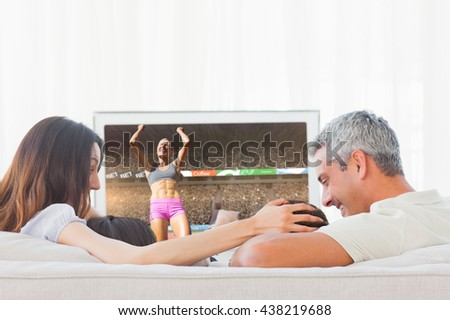 Low angle view of sportswoman celebrating her victory against family watching television together sitting on sofa - stock photo