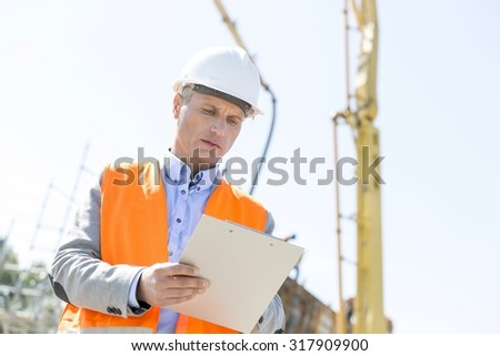 Low angle view of supervisor writing on clipboard at construction site - stock photo